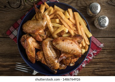 Baked chicken wings with french fries on wooden table. Top view.