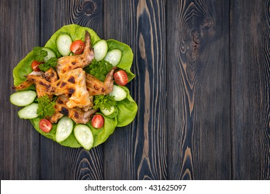Baked chicken wings with green salad leaves on a wooden table , close-up view
