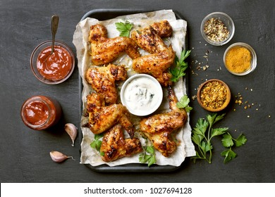 Baked chicken wings on baking tray over black background. Top view, flat lay