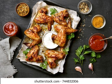 Baked chicken wings on baking tray over dark stone background, top view
