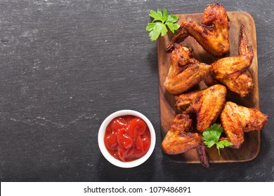 baked chicken wings on wooden board, top view