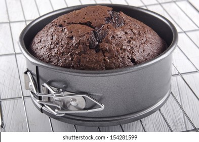 baked chocolate cake in a round baking tin
