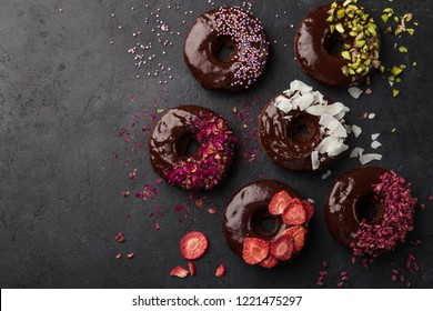 baked chocolate donuts with various topping, top view, dark background, copy space