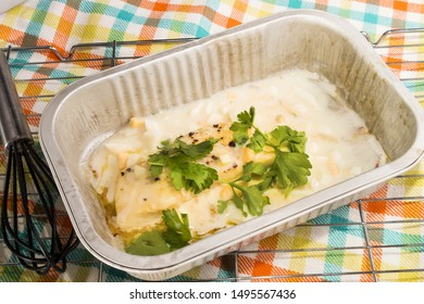 baked cod with parsley in a small aluminum bowl