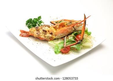 Baked crayfish on white dish against white background
