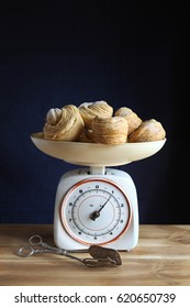 Baked cruffin pastry on a vintage kitchen scale with silver plated serving tong
