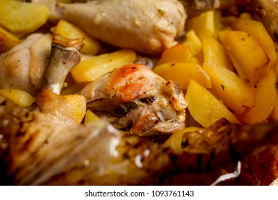 Baked delicious rabbit with potatoes and carrot in a rustic style. A homemade dietary rabbit baked with potatoes close-up in a baking dish on a table. Vertical top view from above. Baked rabbit