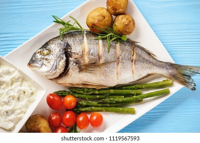 Baked dorado fish with potatoes, asparagus and tomatoes.