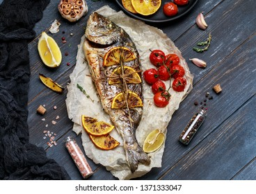 Baked dorado fish. Raw dorado fish and ingredient for cooking. Fresh fish gilt-head bream dorade with salt, herbs and pepper.