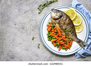 Baked dorado or sea bream with spring vegetables on a vintage plate on grey slate,stone or concrete background.Top view.