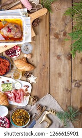 Baked duck and various snacks for the Christmas table. Rustic table with decor and different food for the holiday. Top view. Free space for text. Baking dish with a pattern