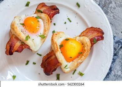 Petit-déjeuner à l'oeuf cuit avec bacon et toast en forme de coeur pour la Saint-Valentin