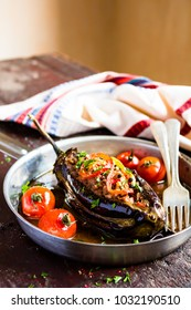 Baked eggplant or aubergine stuffed with pork and beef meat, red hot chili pepper with roasted cherry tomatoes and fresh parsley in a cooking pan on a wooden table, selective focus. Turkish food.