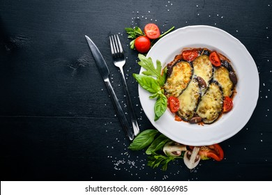 Baked eggplant with parmesan cheese. On a black wooden surface. Free space for your text. Top view.