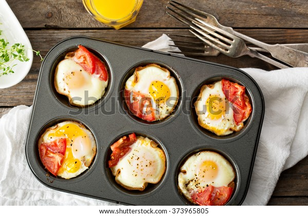 Baked eggs with ham and tomato in muffin tin
