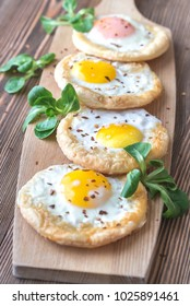 Baked eggs in puff pastry on the wooden board