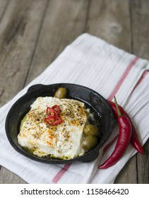 Baked Feta cheese with spices, olives and red pepper  in a cast-iron frying pan on a wooden rustic background. A dish of Greek cuisine. Close up, copy space