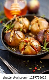 Baked figs stuffed with gorgonzola cheese, pine nuts, honey and herbs in a black dish on a dark, stone background. Excellent, tasty, vegetarian snack, appetizer