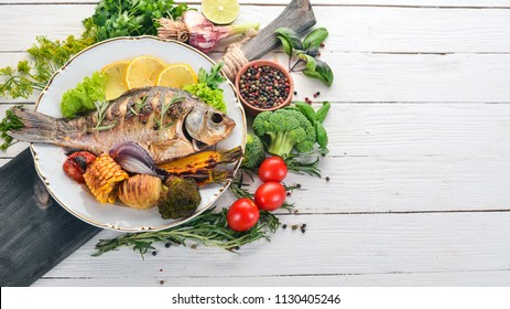 Baked fish carp. On a wooden background. Top view. Copy space.