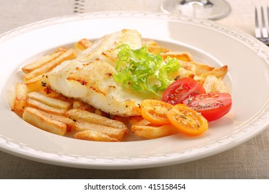 Baked fish and chips on elegant plate