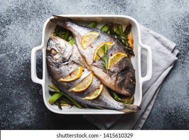 Baked fish dorado with green asparagus in white ceramic baking pan on gray rustic concrete background, top view. Healthy dinner with fish concept, dieting and clean eating