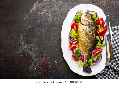 Baked fish dorado. Dorado fish oven baked and fresh vegetable salad on plate. Sea bream or dorada fish grilled and vegetable salad