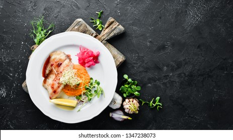Baked fish fillet with mashed sweet potatoes. In the plate. Top view. Free space for your text. Rustic style.