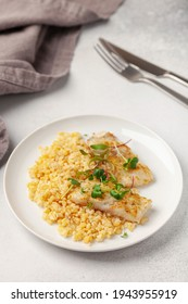 Baked fish hake or pollock and garnish bulgur and microzelenium in a plate on the table. Healthy food