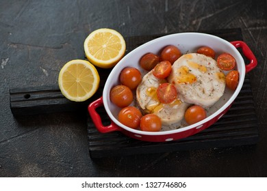 Baked fish medallions with cherry tomatoes and lemon over dark brown stone background, studio shot