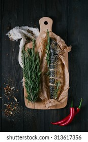 Baked fish on a cutting board with rosemary and spices on a black wooden background