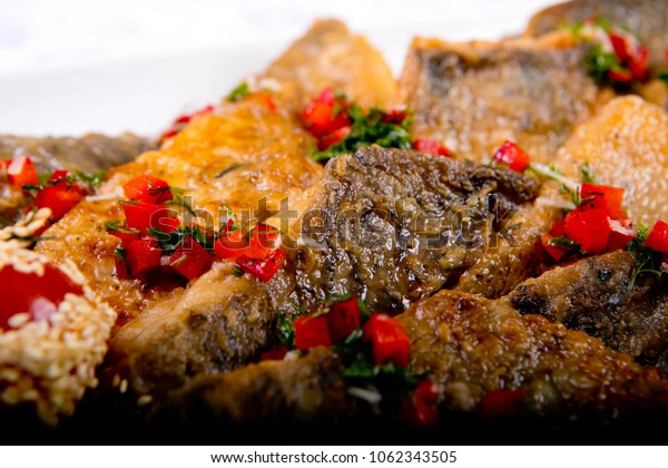 baked fish with red cayenne pepper on the white table