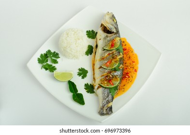 Baked fish with sweet and sour sauce and rise decorated greens and lime on a plate isolated on white background
