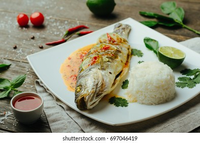 Baked fish with sweet and sour sauce and rise decorated parsley, basil, chile and lime on a plate on wooden background