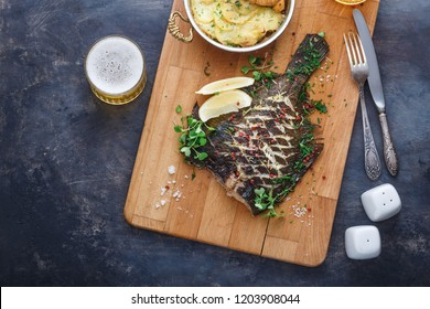 Baked flatfish with potato gratin and beer, copy space
