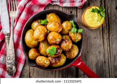 Baked in frying pan whole young potatoes, homemade vegetarian food, wooden old rustic table, with sauce, copy space top view