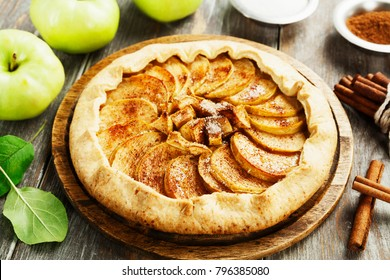 Baked galette or open pie with apples and cinnamon on the table