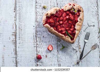 Baked galette or open pie heart shaped with strawberry on white wooden background Healthy homemade whole grain fruit pie. valentines day concept food