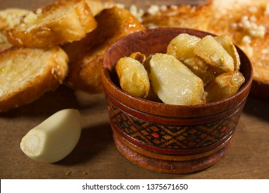 Baked garlic in a wooden bowl on the kitchen wooden table