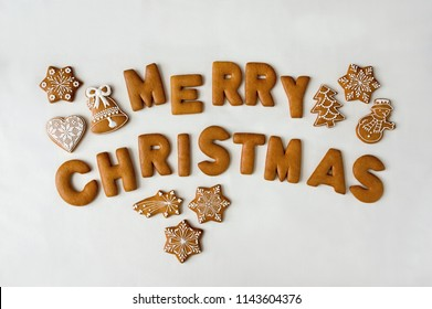 Baked gingerbread cookies letters Merry Christmas and various small decorated gingerbread cookies heart, bell, stars, snowman with white icing on white background