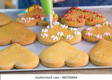 Baked gingerbread on baking pan are decorated with pastry bag