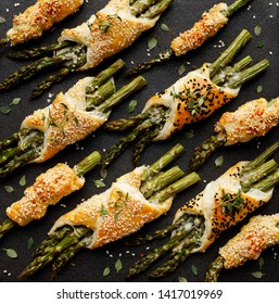 Baked green asparagus in puff pastry sprinkled with sesame seeds, nigella seeds and fresh thyme on a black background, close-up, top view. Puff pastry bundles