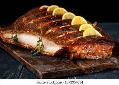 Baked Halibut fish with lemon on wooden board on dark background, hot smoked seafood