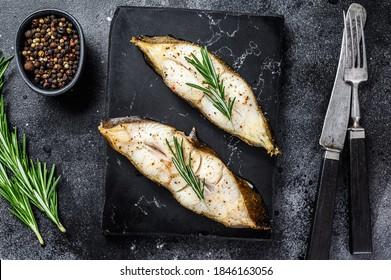 Baked halibut fish steak. Black background. Top view