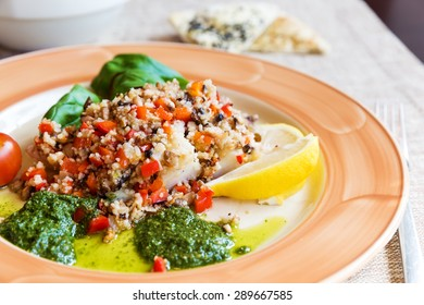 Baked halibut with vegetable garnish and couscous
