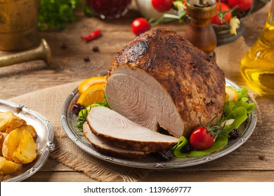 Baked ham, served on an old plate. Natural wooden background. Front view.