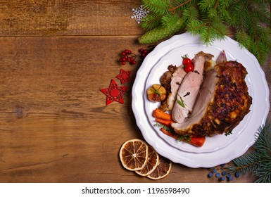 Baked ham with vegetables: carrots, onions, tomatoes, garlic and herbs. Christmas decorations. Dish for Christmas Eve. View from above, top studio shot