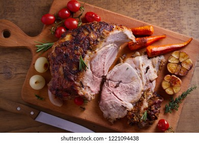 Baked ham with vegetables, rosemary and thyme on chopping board. overhead, horizontal