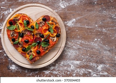 Baked heart-shaped homemade pizza on a cutting board on rustic table, close-up. Happy Valentines day. love concept