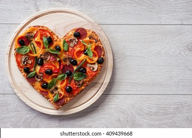 Baked heart-shaped homemade pizza on a cutting board on white wooden background. Close up