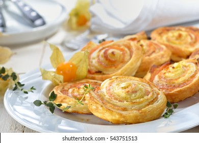 Baked hearty puff pastry rolls with smoked salmon, cream cheese and fresh herbs